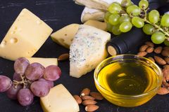 Snacks with wine - bottle, various types of cheeses, figs, nuts, honey, grapes. On a black stone background stock image