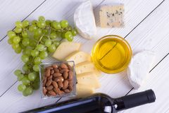 Snacks with wine - bottle, various types of cheeses, figs, nuts, honey, grapes. On a white boards background stock photos