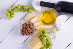 Snacks with wine - bottle, various types of cheeses, figs, nuts, honey, grapes. On a white boards background royalty free stock photos