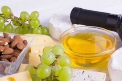 Snacks with wine - bottle, various types of cheeses, figs, nuts, honey, grapes. On a white boards background stock images