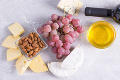 Snacks with wine - bottle, various types of cheeses, figs, nuts, honey, grapes. On a white wooden background stock image