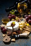 snacks, wine and Camembert cheese on a dark background, vertical Stock Photography