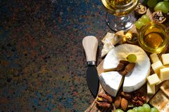 snacks, wine and camembert on a dark background, top view Stock Photo