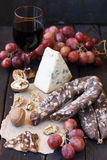 Snacks for wine, cheese with mold, pink grapes, walnuts Royalty Free Stock Photo