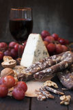 Snacks for wine, cheese with mold, pink grapes, walnuts Royalty Free Stock Photography