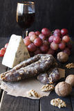 Snacks for wine, cheese with mold, pink grapes, walnuts Royalty Free Stock Images