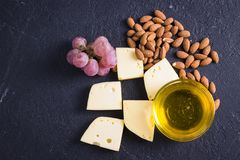 Snacks with wine - various types of cheeses, figs, nuts, honey, grapes. On a black stone background royalty free stock photography