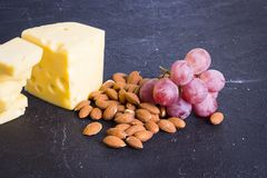 Snacks with wine - various types of cheeses, figs, nuts, honey, grapes. On a black stone background stock photos