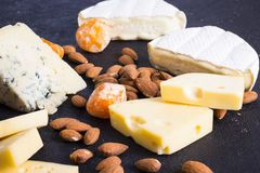 Snacks with wine - various types of cheeses, figs, nuts, honey, grapes. On a black stone background stock image