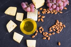 Snacks with wine - various types of cheeses, figs, nuts, honey, grapes. On a black stone background royalty free stock photos