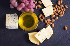Snacks with wine - various types of cheeses, figs, nuts, honey, grapes. On a black stone background royalty free stock image
