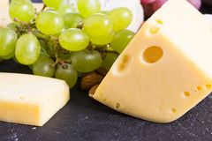 Snacks with wine - various types of cheeses, figs, nuts, honey, grapes. On a black stone background stock photography