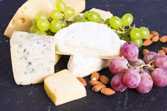 Snacks with wine - various types of cheeses, figs, nuts, honey, grapes. On a black stone background stock photo