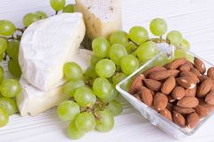 Snacks with wine - various types of cheeses, figs, nuts, honey, grapes. On a white boards background royalty free stock images