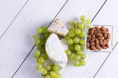 Snacks with wine - various types of cheeses, figs, nuts, honey, grapes. On a white boards background royalty free stock photo
