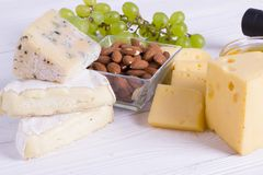Snacks with wine - various types of cheeses, figs, nuts, honey, grapes. On a white boards background stock photography