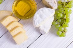 Snacks with wine - various types of cheeses, figs, nuts, honey, grapes. On a white boards background royalty free stock image