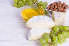 Snacks with wine - various types of cheeses, figs, nuts, honey, grapes. On a white boards background stock photo