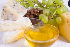 Snacks with wine - various types of cheeses, figs, nuts, honey, grapes. On a white boards background royalty free stock photography