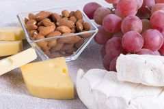 Snacks with wine - various types of cheeses, figs, nuts, honey, grapes. On a white wooden background royalty free stock image
