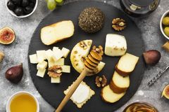 Snacks with wine - various types of cheeses, figs, nuts, honey, Stock Image