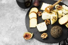 Snacks with wine - various types of cheeses, figs, nuts, honey, Stock Photo