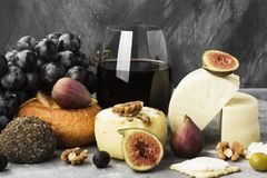 Snacks with wine - various types of cheeses, figs, nuts, honey, Stock Photography