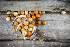 Snacks on wood. Sweets nuts with colored sugar coat in vintage bowl on wood, top view Royalty Free Stock Photos