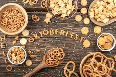 Snacks on wooden table. Word Oktoberfest made of salty crackers. Letters Stock Image