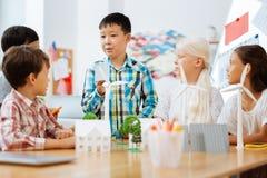 Snacksalig pojke som talar med klasskompisar i ett klassrum royaltyfria foton
