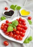 Snacktomaten, basilicum, olie en azijn om een gezonde salade te maken Stock Afbeeldingen