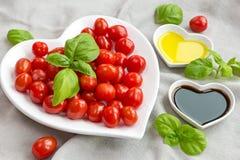 Snacktomaten, basilicum, olie en azijn om een gezonde salade te maken Stock Fotografie