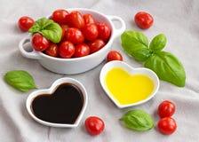 Snacktomaten, basilicum, olie en azijn om een gezonde salade te maken Stock Foto