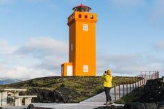 SNAEFELLSNES, donna in impermeabile giallo che prende immagine del faro di Svortuloft, penisola di Snaefellsnes, Islanda fotografia stock libera da diritti