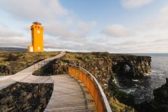 SNAEFELLSNES, ICELAND - AUGUST 2018: view over orange tower of Svortuloft Lighthouse. And arch in the cliff royalty free stock photos