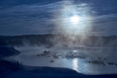 Snags in the river water in  winter Moon night. Blue fog backlit by mystical Moonlight Royalty Free Stock Photography