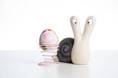 Snail with egg. Ceramic snail looking at you beside an Easter egg Royalty Free Stock Photography
