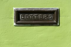 Snail mail. Old mail letter box in a distressed green house front door Royalty Free Stock Photos