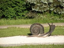 Snail. Sculpture.Landscape area in the rays of the setting sun. royalty free stock image