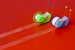 Snails. Two small colored scotch tape dispensers with pins on a red background as a couple of snails in a competition Stock Photo