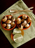 Snails with Garlic Butter. Two Bowls of Delicious Escargot with Garlic Butter, Silver Forks and Sliced Lime closeup on Green Napkin. Top View Stock Photos
