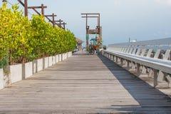 Snak houten brug in het overzees langs kant met groene struik en houten bank met blauwe hemel op de achtergrond royalty-vrije stock afbeeldingen