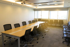 Snak houten lijst en heel wat stoel in grote vergaderzaal met het zonlicht van de projectorpresentatie van venster stock afbeeldingen