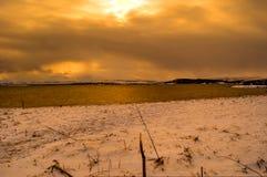 Snak sneeuw overzeese kust in de noordpoolcirkelwintertijd tijdens gouden zonsondergang over sneeuwbergpieken Stock Foto's