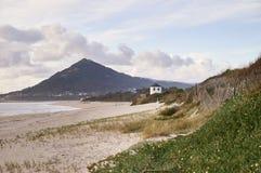 Snak strand tot de heuvel, met een windmolen op het duin stock foto