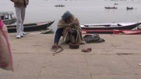 Snake charmer enchanting cobra in a ghat of Varanasi, India, December 26, 2012 stock video footage