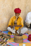 Snake Charmer, People From India, Travel Scene. A snake charmer Indian in India plays a musical instrument to entice his snake into a trance. The man plays for Royalty Free Stock Photo