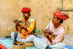 A snake charmer is playing the flute for the cobra Stock Image