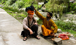 Snake charmers. Hindu man put a snake on the head of a tourist in the middle of a festival in North of India royalty free stock image