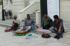 Snake charmers at Singapore. Snake charmers on the pavement at Singapore waiting for the customers Royalty Free Stock Photos